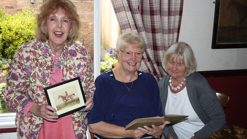 Members show off a book and painting